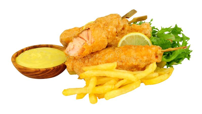 Battered salmon fish fillets on wooden skewers with French Fries. With a wooden bowl of mayonnaise isolated on a white background royalty free stock photos