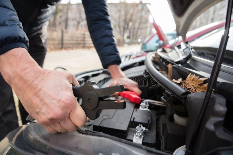 Batteri för ` s för Person Using Jumper Cables To laddningsbil dött fotografering för bildbyråer