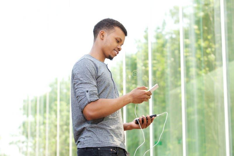 Batteri och mobiltelefon för ung afrikansk amerikanman hållande yttre royaltyfria foton