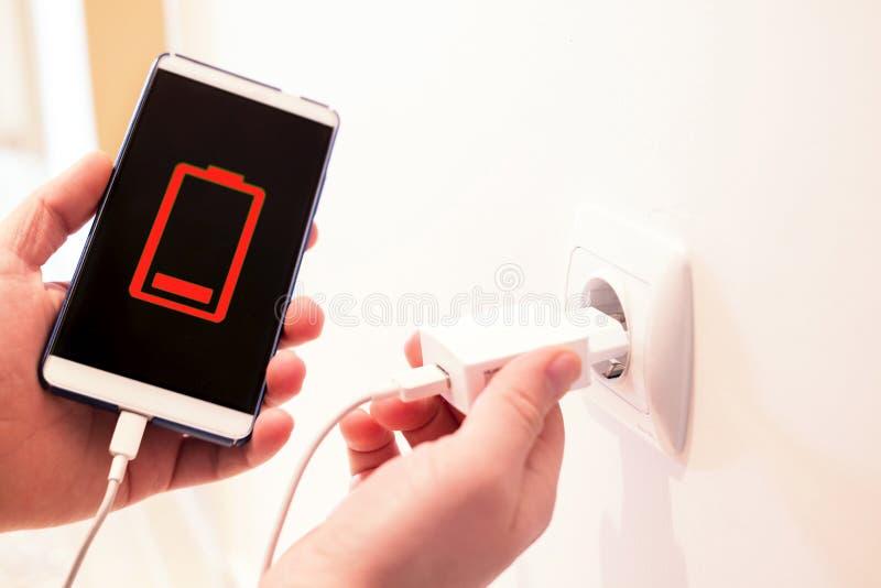 Batteri ut ur telefonen telefon som laddar från ett vägguttag arkivbilder