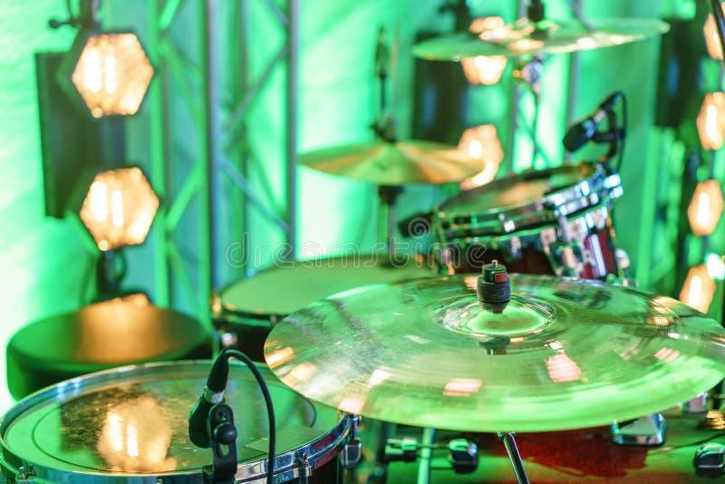 Batteria in scena Primo piano del piatto, tamburi, bastoni, nei riflettori di scena del fondo immagine stock