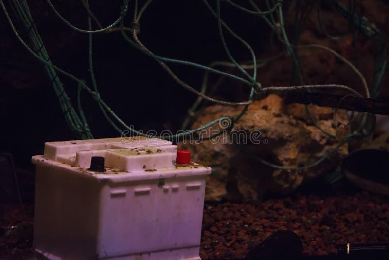 Batterie automobile, plastiques et autres déchets déversés dans la mer images libres de droits