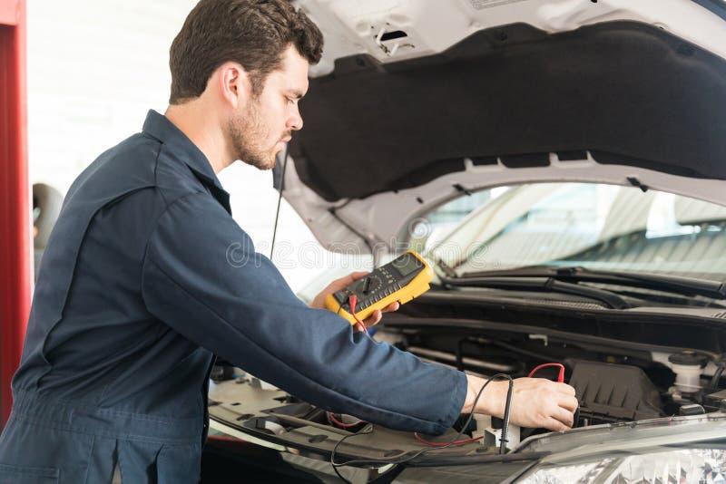Batterie de voiture d'essai de With Digital Multimeter de mécanicien automobile images stock
