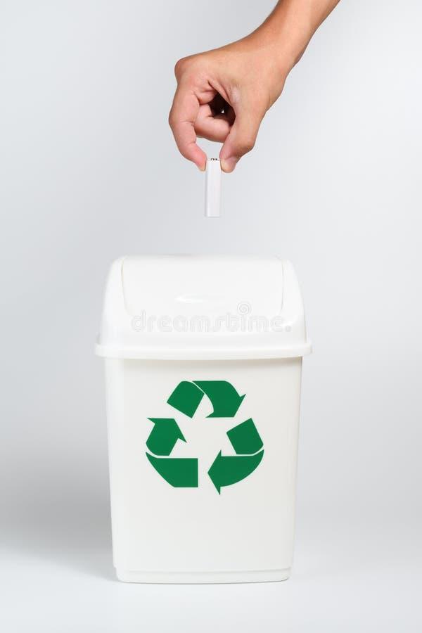 Batterie in der Hand über Papierkorb lizenzfreie stockbilder