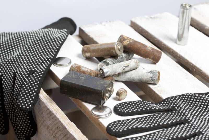 Batterie utilizzate della dito-ferita coperte di corrosione Si trovano su una scatola di legno Guanti di lavoro seguenti riciclag fotografie stock libere da diritti