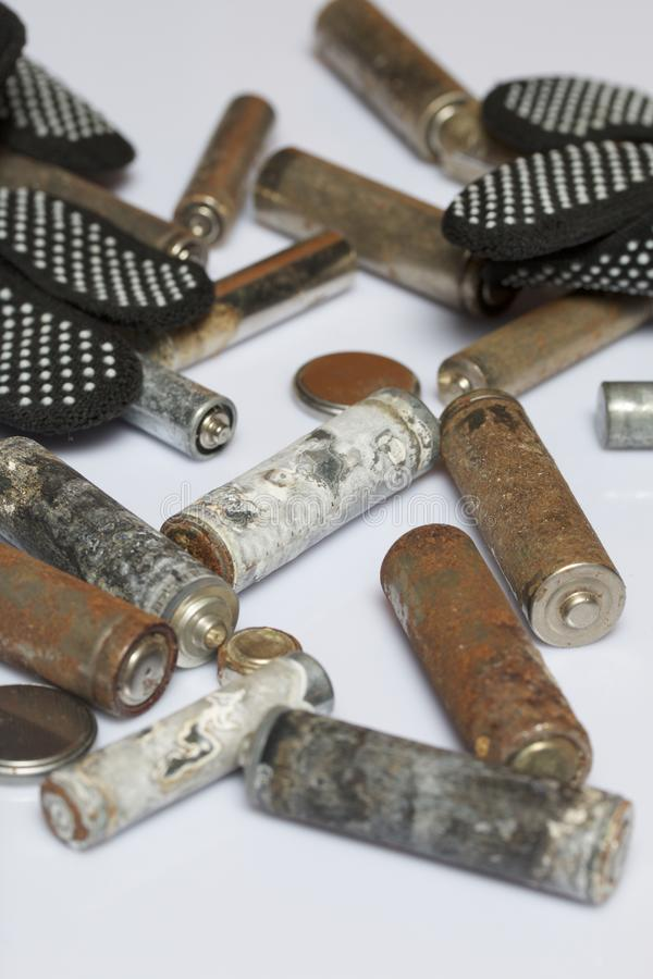Batterie utilizzate della dito-ferita coperte di corrosione Si trovano su una scatola di legno Guanti di lavoro seguenti riciclag fotografia stock