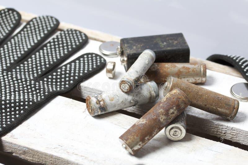 Batteries utilisées de doigt-blessure couvertes de corrosion Ils se trouvent sur une boîte en bois Prochains gants fonctionnants  images libres de droits