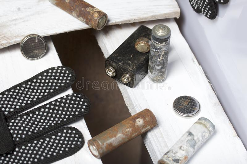 Batteries utilisées de doigt-blessure couvertes de corrosion Ils se trouvent sur une boîte en bois Prochains gants fonctionnants  images stock