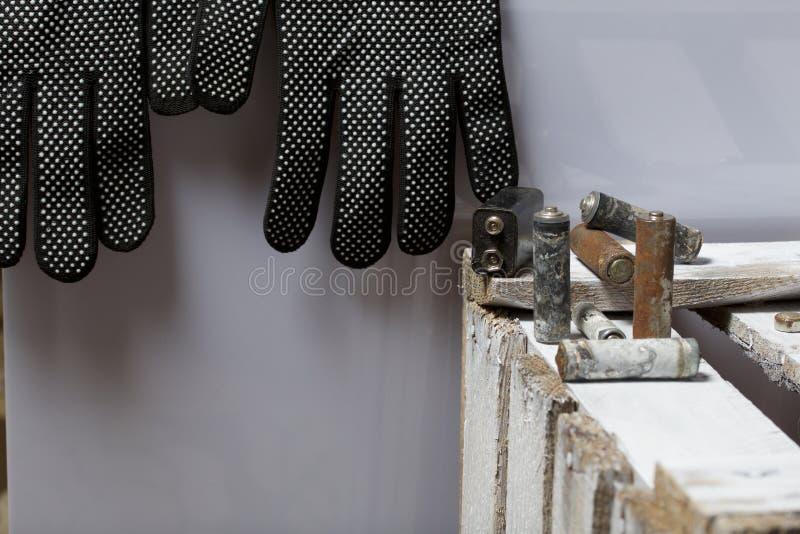 Batteries utilisées de doigt-blessure couvertes de corrosion Ils se trouvent sur une boîte en bois Prochains gants fonctionnants  image stock