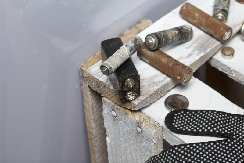 Batteries utilisées de doigt-blessure couvertes de corrosion Ils se trouvent sur une boîte en bois Prochains gants fonctionnants  image libre de droits
