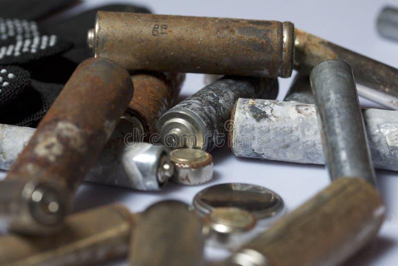 Batteries utilisées de doigt-blessure couvertes de corrosion Ils se trouvent sur une boîte en bois Prochains gants fonctionnants  photos libres de droits