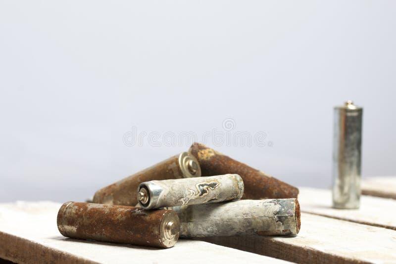 Batteries utilisées de doigt-blessure couvertes de corrosion Ils se trouvent sur une boîte en bois réutilisation images libres de droits