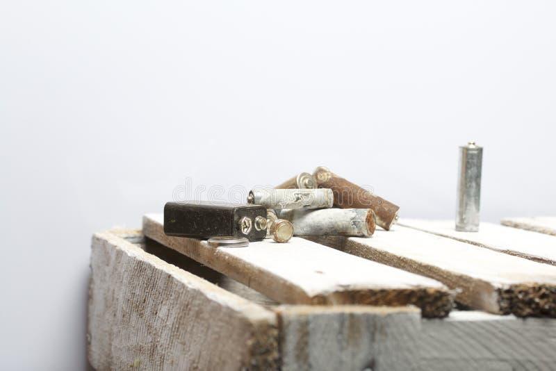 Batteries utilisées de doigt-blessure couvertes de corrosion Ils se trouvent sur une boîte en bois réutilisation photo libre de droits