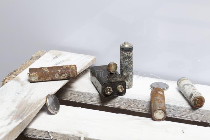 Batteries utilisées de doigt-blessure couvertes de corrosion Ils se trouvent sur une boîte en bois réutilisation photos libres de droits