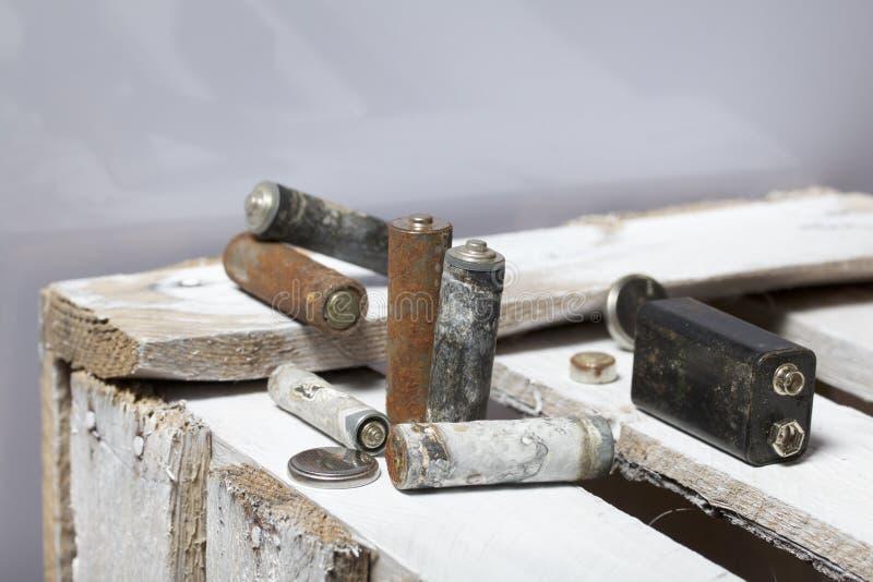 Batteries utilisées de doigt-blessure couvertes de corrosion Ils se trouvent sur une boîte en bois réutilisation photos stock