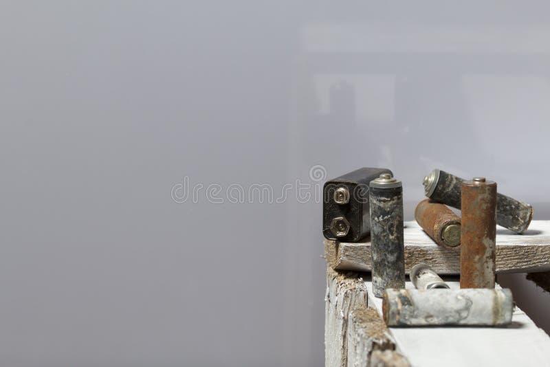 Batteries utilisées de doigt-blessure couvertes de corrosion Ils se trouvent sur une boîte en bois réutilisation photographie stock