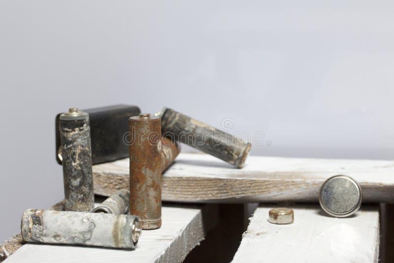Batteries utilisées de doigt-blessure couvertes de corrosion Ils se trouvent sur une boîte en bois réutilisation photographie stock libre de droits