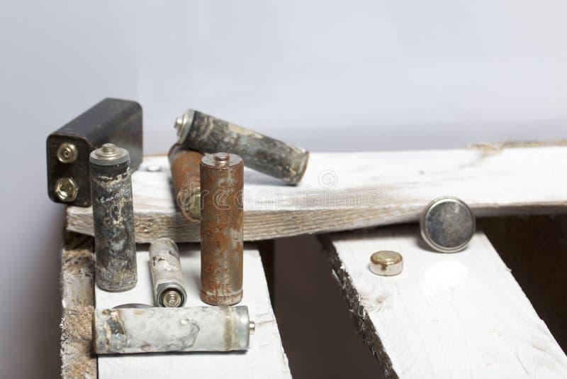 Batteries utilisées de doigt-blessure couvertes de corrosion Ils se trouvent sur une boîte en bois réutilisation images stock