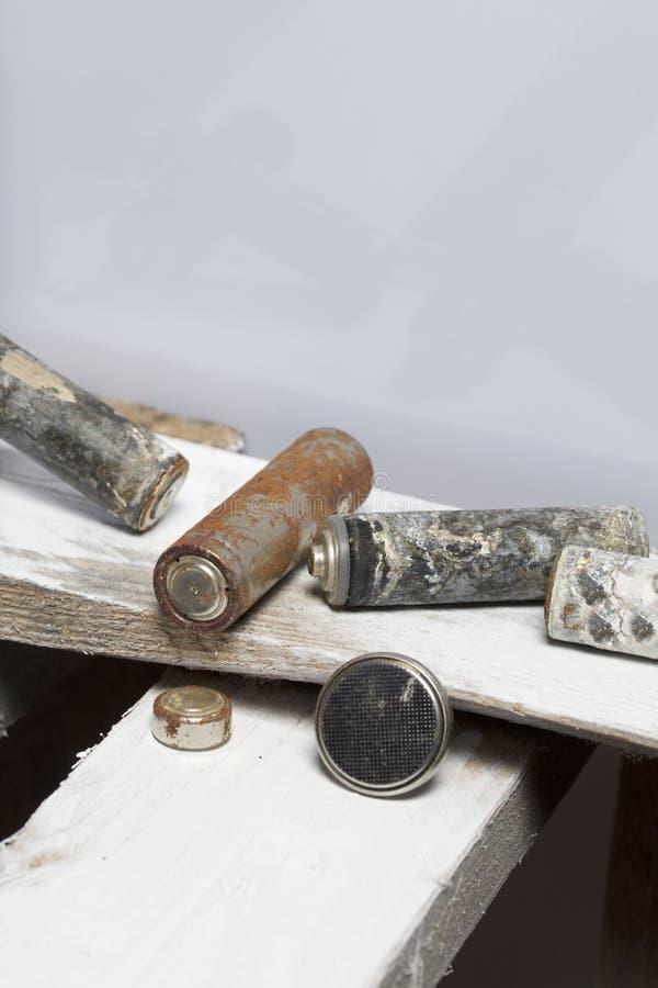 Batteries utilisées de doigt-blessure couvertes de corrosion Ils se trouvent sur une boîte en bois réutilisation image stock