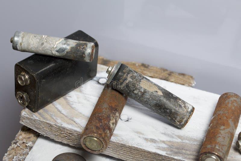 Batteries utilisées de doigt-blessure couvertes de corrosion Ils se trouvent sur une boîte en bois réutilisation photo stock