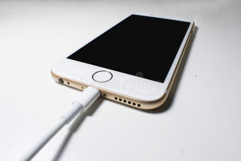 Batterijlader die in de telefoon wordt gestopt Witte achtergrond royalty-vrije stock foto
