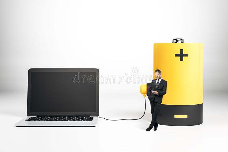 Battery charging empty laptop. Businessman standing next to battery charging empty laptop on gray background. Energy and technology concept. Mock up, 3D royalty free illustration