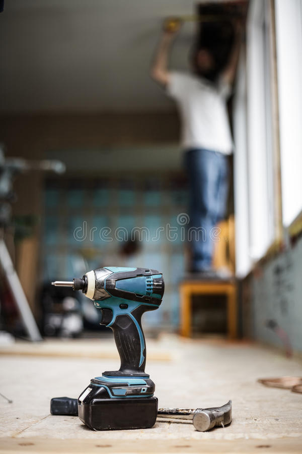 Battery Drill on the Floor. With Worker in Background royalty free stock image