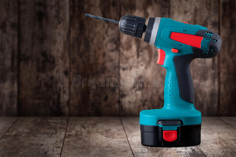 Battery drill. On a wooden background royalty free stock images