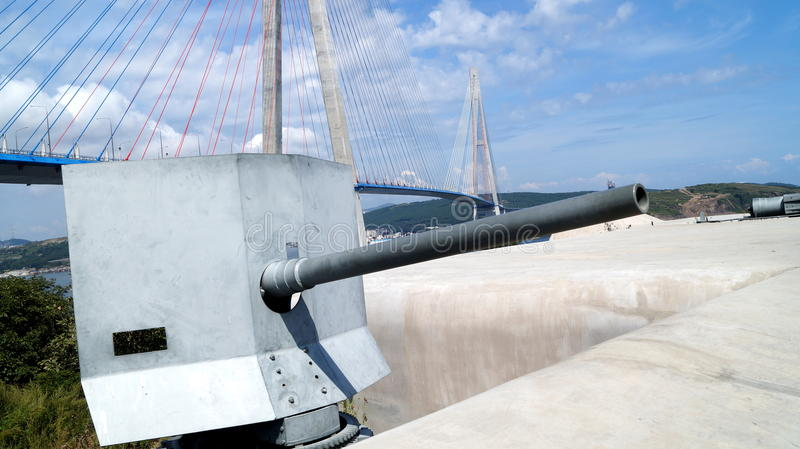 Battery number 375 `Novosiltsevskaya`. Island Russky, Primorsky Territory. 57-mm Nordenfeld coastal cannon against the background of the bridge to the Russky stock photography