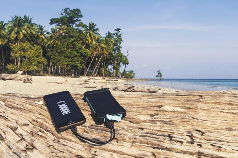 Battery solar energy device on a background. Of the sandy beach of an uninhabited island. Charge smart phone from the solar battery. the solar battery lies on a stock photos
