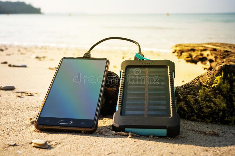Battery solar energy device on a background. Of the sandy beach of an uninhabited island. Charge smart phone from the solar battery. the solar battery lies on a royalty free stock photography