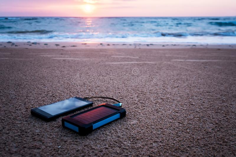 Battery solar energy device on a background. Of the sandy beach of an uninhabited island. Charge smart phone from the solar battery. beautiful tropical sunset stock photography