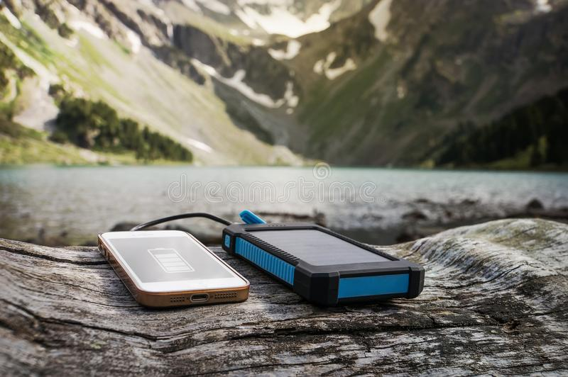 Battery solar energy device on the stone. Battery solar energy device on the background of beautiful mountain scenery. Charge smart phone from the solar battery royalty free stock images