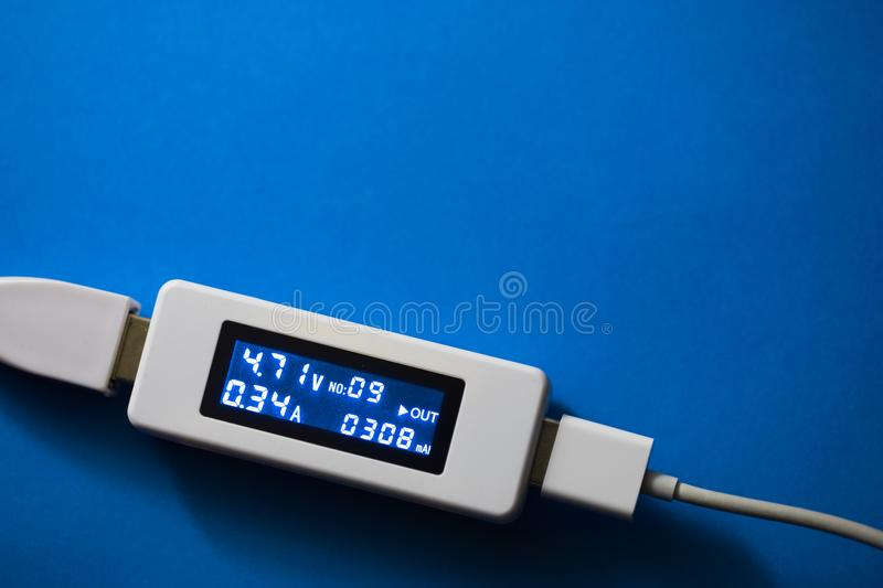 Battery tester diagnostic tool, blue background. With copy-space stock photos