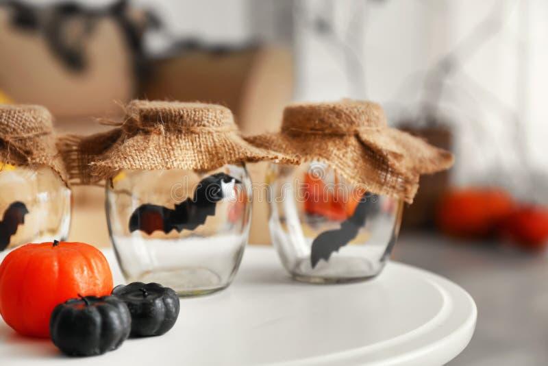 Battes de papier dans des pots avec des bougies comme décor pour la partie de Halloween sur la table image libre de droits