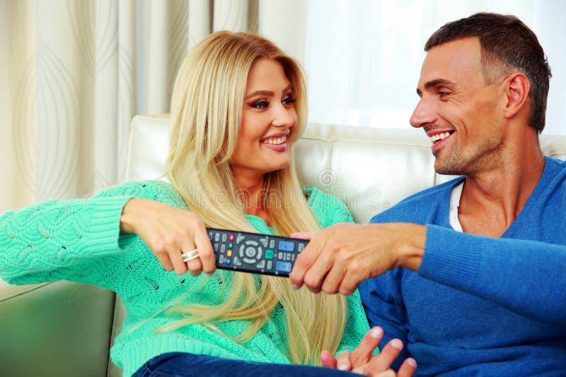 Battibecco delle coppie per cambiare canale televisivo immagine stock