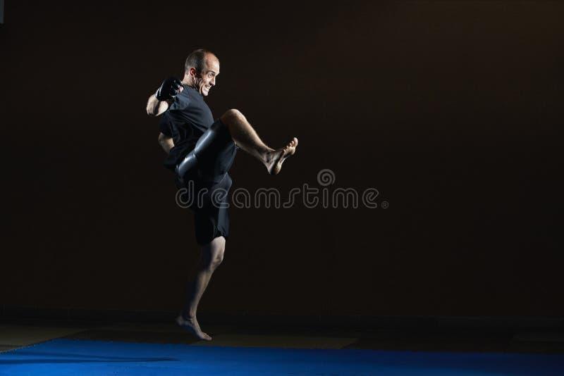 Battiti dell'uomo forte con una gamba di scossa fotografia stock libera da diritti