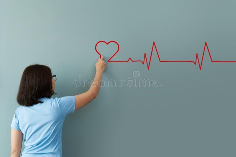 Battito cardiaco del disegno della donna con gesso rosso sulla parete fotografia stock