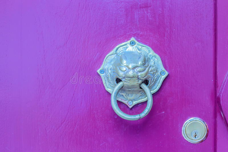 Battitore di porta dorato sotto forma del leone con l'anello su un legno rosso immagine stock libera da diritti