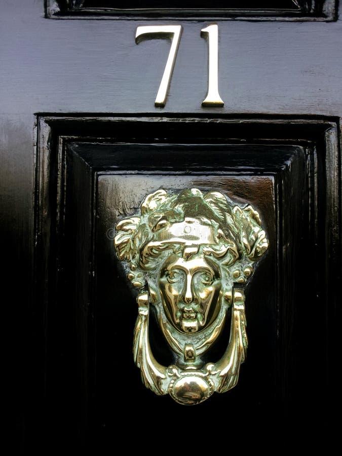 Battitore sulla porta nera numero 71 con il fronte dorato immagini stock
