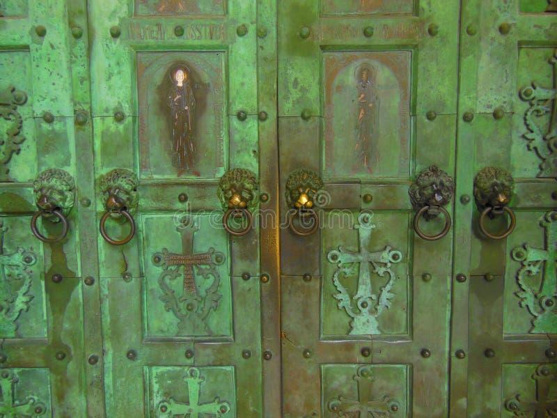 Battitori capi del leone sulla vecchia porta immagine stock