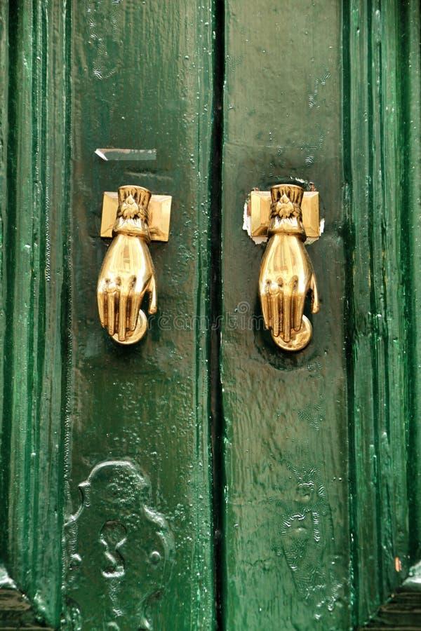 Battitori di porta con forma della mano sulla porta di legno verde immagini stock libere da diritti
