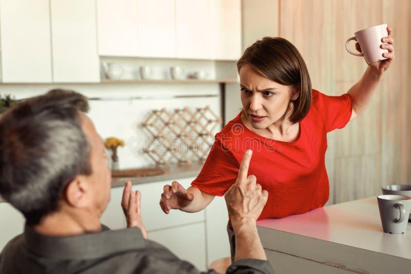 Battitura di moglie dai capelli corti furiosa pazza il suo marito spaventato immagini stock
