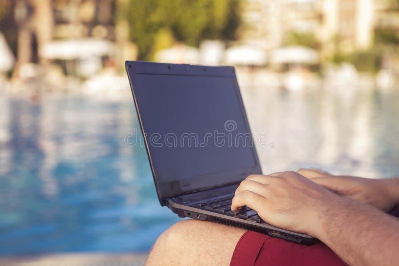 Battitura a macchina di lavoro dell'uomo d'affari su un computer portatile sulla sua vacanza immagine stock libera da diritti
