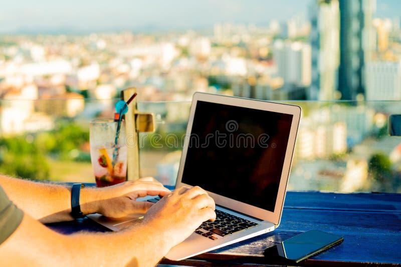 Battitura a macchina maschio su un computer portatile in un caffè sul tetto di un palazzo multipiano con una bella vista panorami immagine stock
