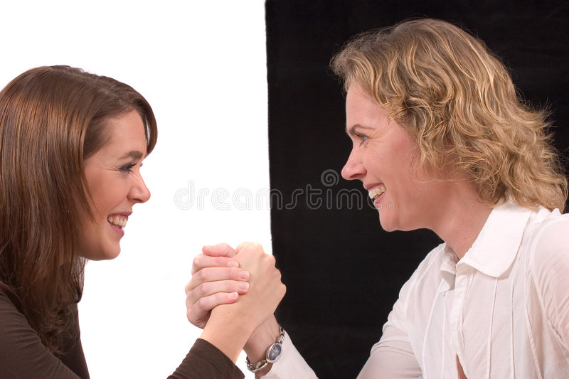 Battle between black & white. Girlfriends doing some armwrestling stock photo
