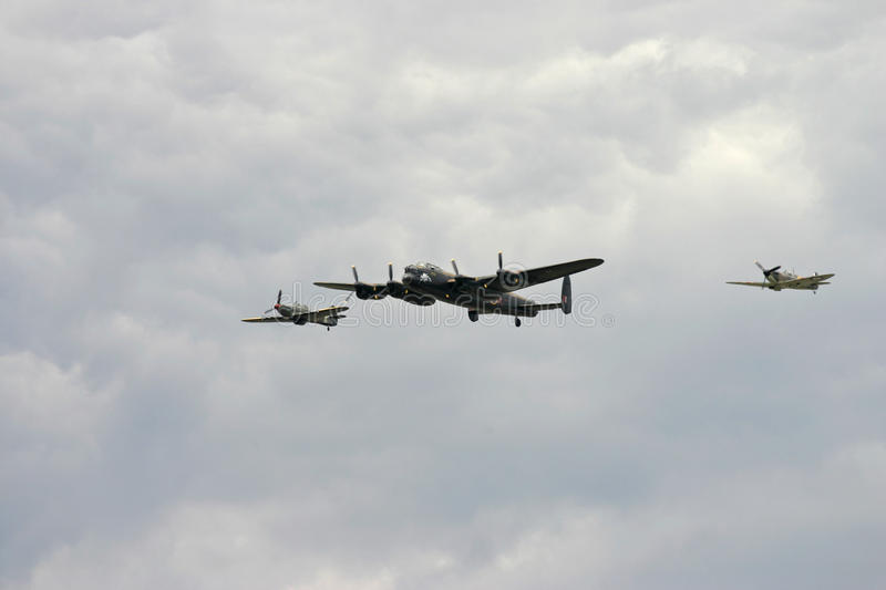 Battle of Britain Flight featuring a Lancaster WW2 bomber and a Hurricane and Spitfire. In close formation in a cloudy sky royalty free stock photo