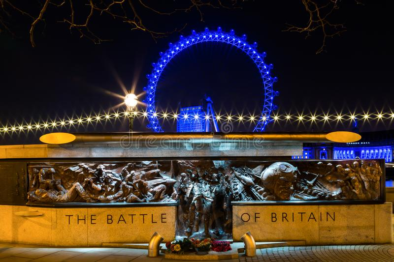 London, London / United Kingdom - March 7, 2014:The Battle Of Britain Memorial at night with the blue London Eye in the background.  royalty free stock image