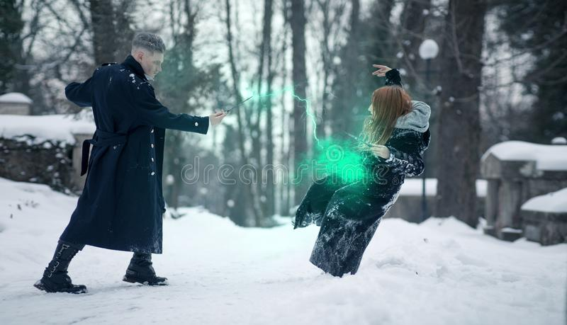 Battle of dark and light magicians with the help of magic wands and green beam. On the snow background stock image
