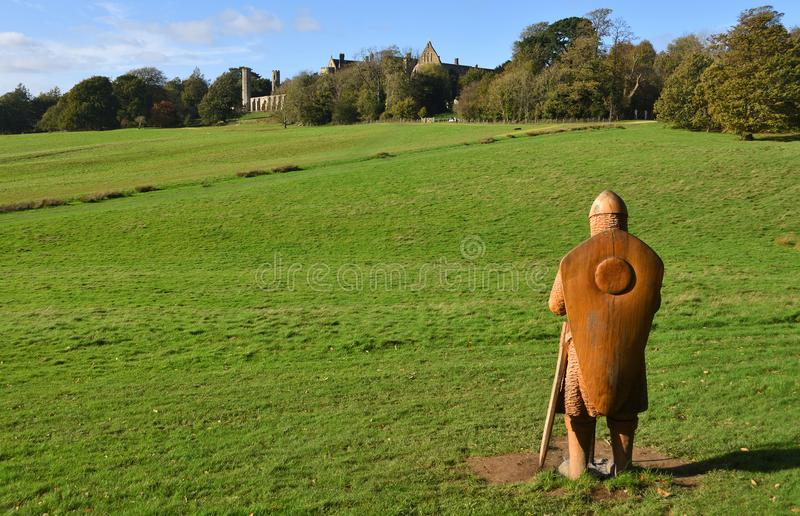 The Battle of Hasting Battle site with Battle Abbey in the background and full size carved wooden soldier in foreground. royalty free stock photography